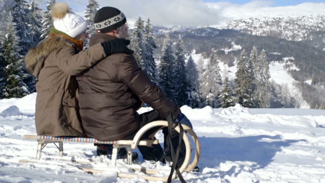 senior couple enjoying in snow with sledge - innsbruck stock videos and b-roll footage