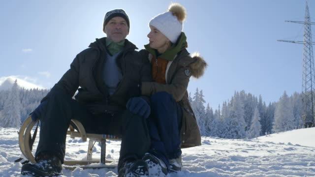 Senior couple enjoying in snow with sledge