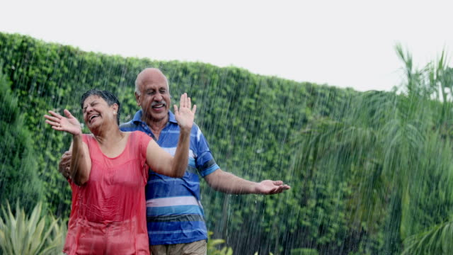 senior couple enjoying in the rain season, delhi, india - exhilaration stock videos & royalty-free footage