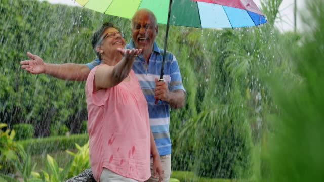 vídeos y material grabado en eventos de stock de senior couple enjoying in the rain season, delhi, india - camisa de polo