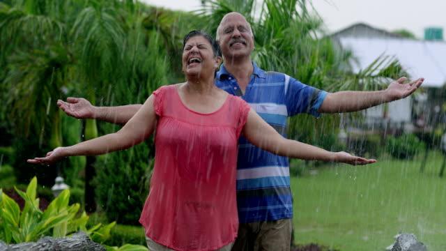 senior couple enjoying in the rain season, delhi, india - ritemprarsi video stock e b–roll