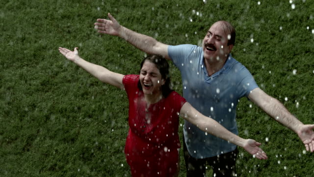 senior couple enjoying in the rain season, delhi, india - baffo peluria del viso video stock e b–roll