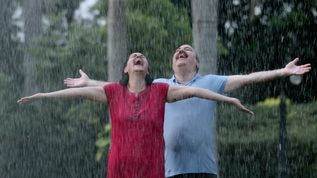 vídeos y material grabado en eventos de stock de senior couple enjoying in the rain season, delhi, india - 60 64 años
