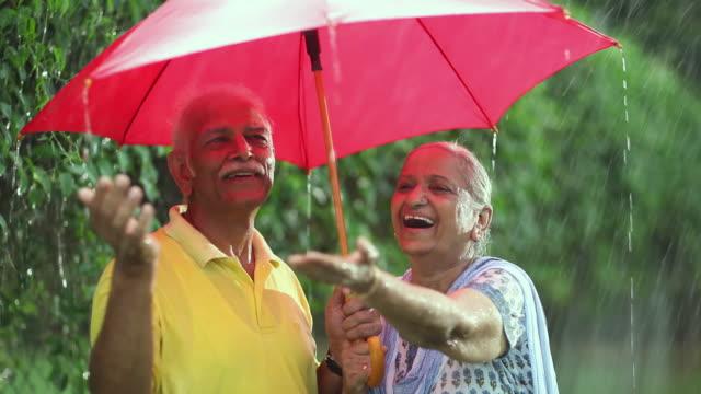 Senior couple enjoying in the rain