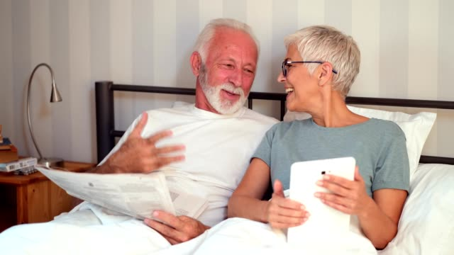 senior couple enjoying lazy morning - old newspaper stock videos and b-roll footage