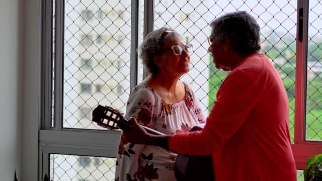 vídeos de stock, filmes e b-roll de casal de idosos curtindo canto e violão - cantar
