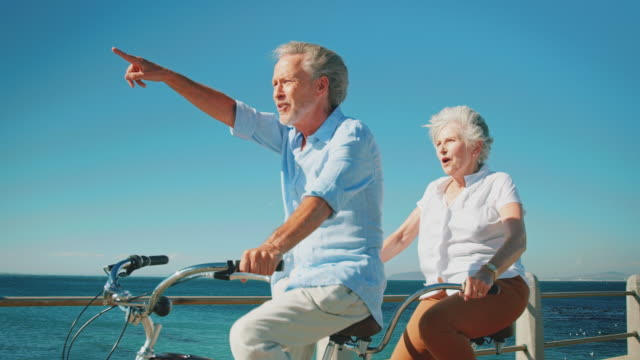 Senior couple enjoying tandem bicycle on sunny day