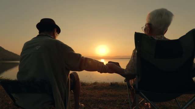 senior couple enjoying the sunset view at the lake, slow motion - enjoyment stock videos & royalty-free footage