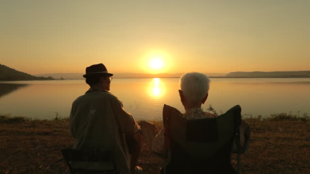 senior couple enjoying the sunset view at the lake, slow motion - standing water stock videos & royalty-free footage