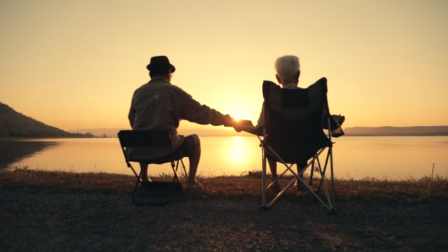 vídeos de stock e filmes b-roll de senior couple enjoying the sunset view at the lake, slow motion - pôr do sol