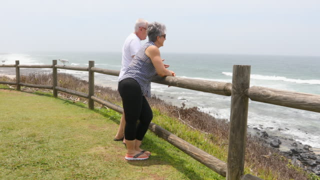 senior couple enjoying the view at a pristine wilderness beach - leisure activity stock videos & royalty-free footage