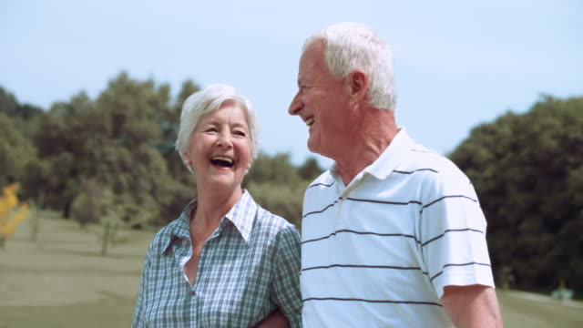 slo mo senior couple enjoying their walk in the park - active seniors stock videos & royalty-free footage