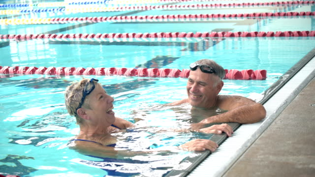 senior couple exercising together, swimming laps - indoors stock videos & royalty-free footage