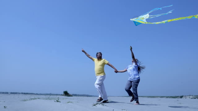 Senior couple flying kite on the sand, Haryana, India