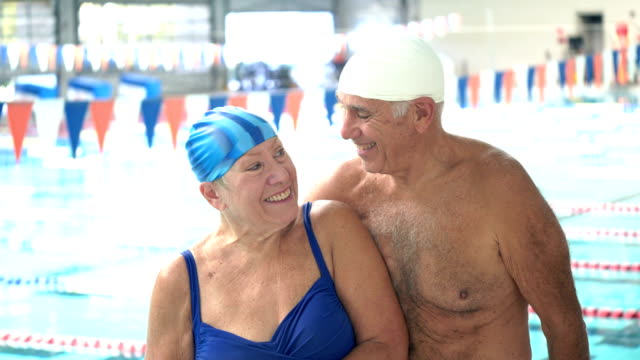 senior couple, fun staying fit together at swimming pool - candid stock videos & royalty-free footage