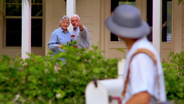 vidéos et rushes de ms senior couple gardening by house waving to mailman delivering mail - facteur