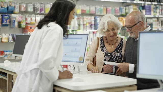 senior couple giving prescription to pharmacist - pharmacy stock videos & royalty-free footage