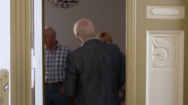 senior couple greeting and welcoming guest at doorway - arrivo video stock e b–roll
