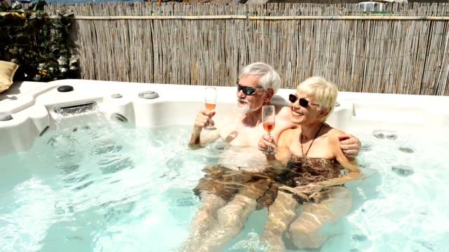 senior couple have fun in a body massage pool - aperitivo video stock e b–roll