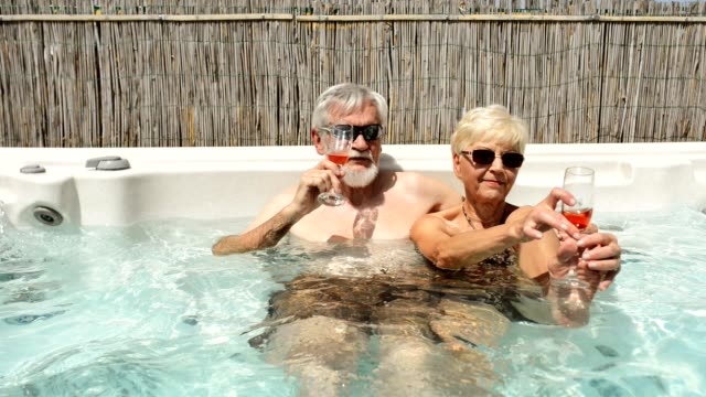senior couple have fun in a body massage pool - mature couple stock videos & royalty-free footage