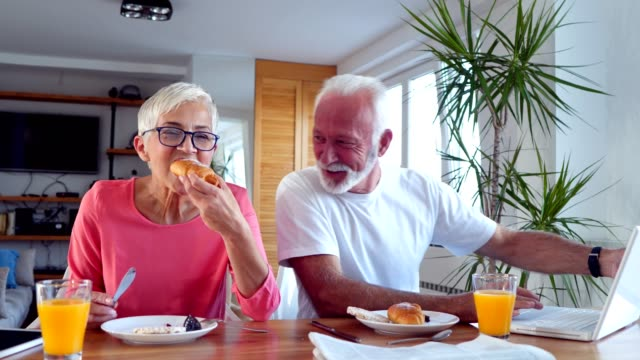 senior couple have relaxing breakfast at home - silver surfer stock videos & royalty-free footage