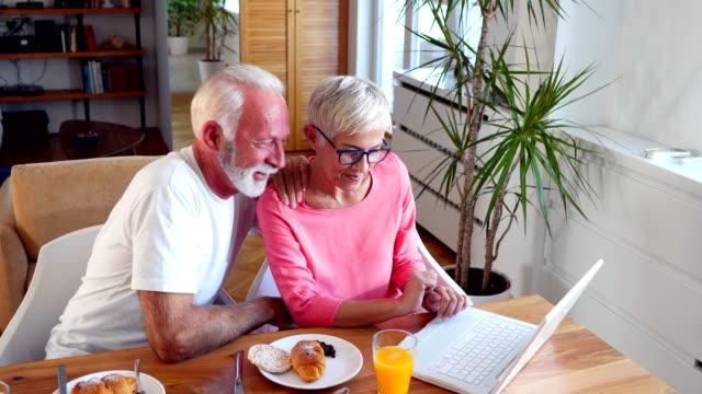 vídeos de stock, filmes e b-roll de casal sênior tem um relaxante pequeno-almoço em casa - idoso na internet