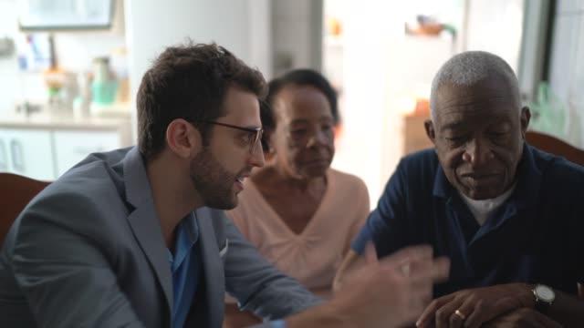 vídeos de stock, filmes e b-roll de casal de idosos tendo uma consulta com um consultor financeiro em casa - consultor financeiro
