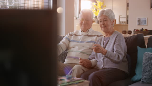 senior couple having a good time watching tv - television set stock videos & royalty-free footage