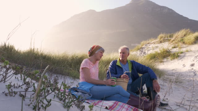 senior couple having a picnic in sand dunes by the beach - mature couple stock videos & royalty-free footage