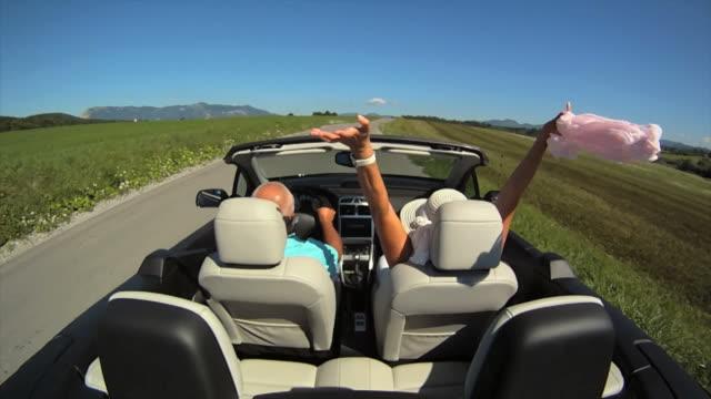 vidéos et rushes de hd ralenti: couple senior ayant une balade - voiture décapotable