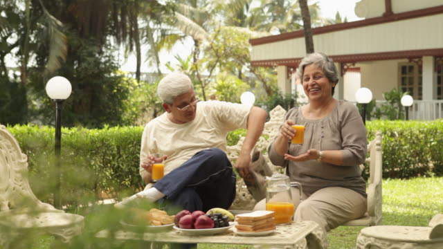 senior couple having breakfast in a lawn  - frühstück stock-videos und b-roll-filmmaterial
