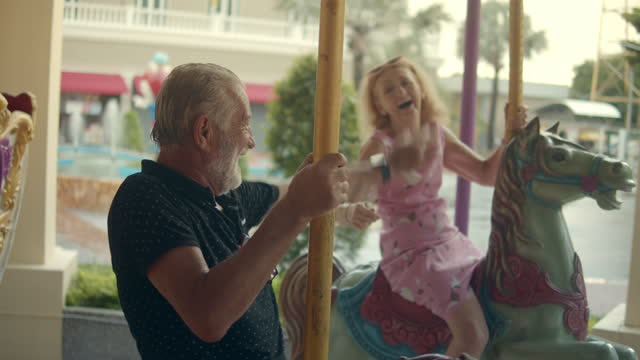senior couple having fun an amusement park,slow motion - roundabout stock videos & royalty-free footage