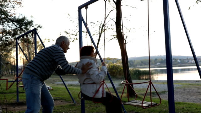 senior couple having fun on the swing - swinging stock videos & royalty-free footage
