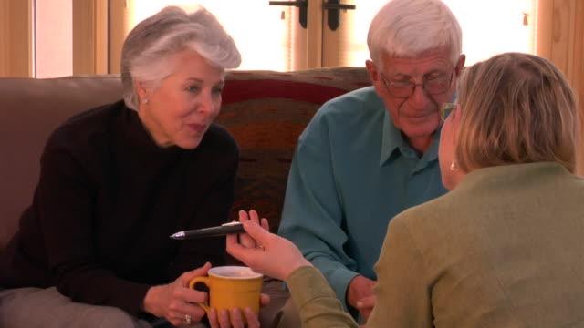 zo, ms, senior couple having meeting with financial advisor, santa fe, new mexico, usa - 説得点の映像素材/bロール