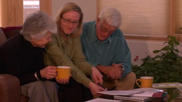 ms, senior couple having meeting with financial advisor, santa fe, new mexico, usa - 説得点の映像素材/bロール