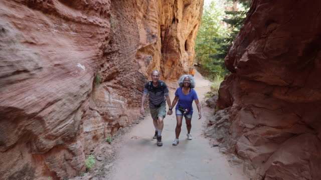 vídeos de stock e filmes b-roll de 4k uhd: senior couple hiking through canyon - parque natural