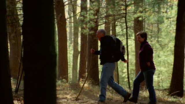 Senior couple hiking uphill in woods
