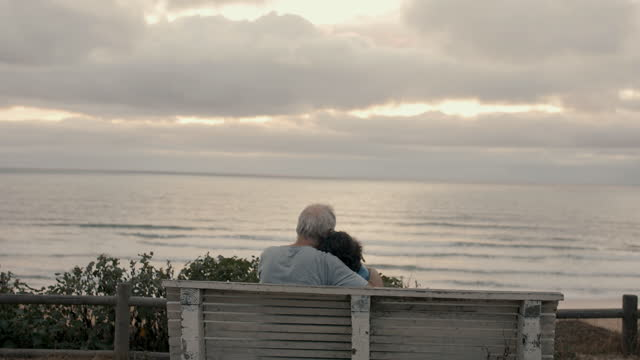 senior couple holding each other watching the sea at beach - married stock videos & royalty-free footage