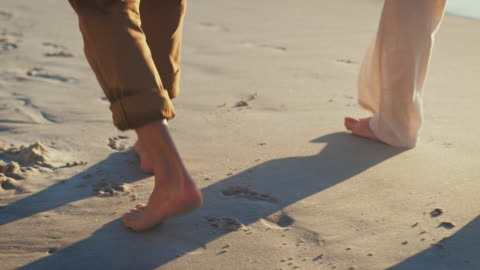 senior couple holding hands on sea shore at beach - affectionate stock videos & royalty-free footage