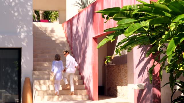 vídeos de stock, filmes e b-roll de ms senior couple holding hands while ascending stairs in courtyard of tropical resort - yucatán