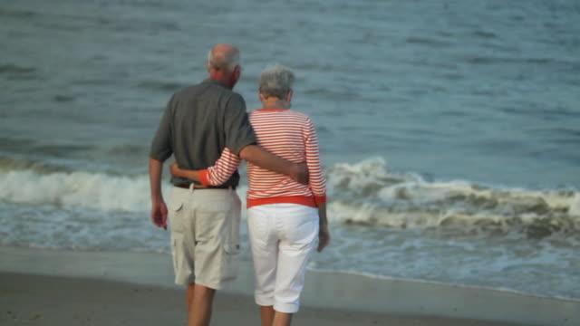 stockvideo's en b-roll-footage met ms pan senior couple hugging on beach and looking at ocean / millville, delaware, usa - activiteit
