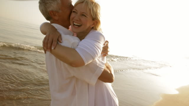senior couple hugging on beach