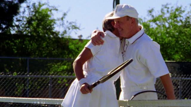 Senior couple hugging over tennis net after match then walking away