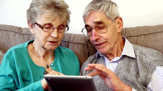 Senior couple in 70s using a digital tablet at home.
