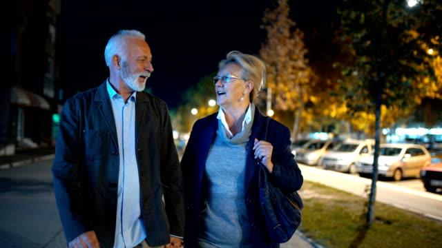 Äldre par i en avkopplande natt promenad.