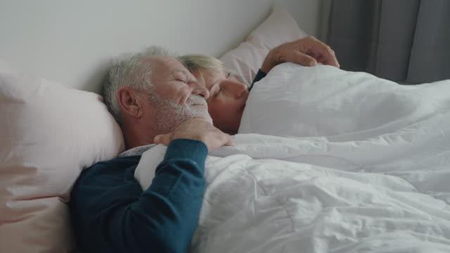 vídeos de stock, filmes e b-roll de casal sênior na cama juntos. - deitando