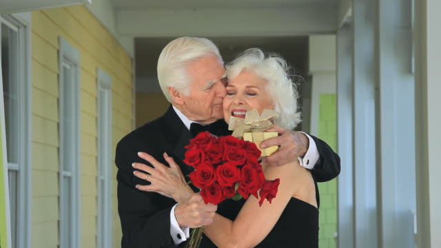 MS Senior couple in formalwear, husband surprising wife with roses and gift, Eastville, Virginia, USA