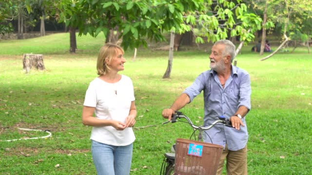 senior couple in love enjoying togetherness at park ,retired couple ride bike in the park together - hugging self stock videos & royalty-free footage
