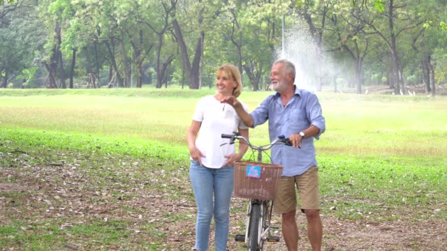 Senior couple in love enjoying togetherness at park ,Retired couple ride bike in the park together