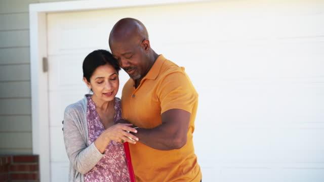vídeos de stock, filmes e b-roll de um par sênior no amor que abraça e que fala quando estão estando na frente de sua casa. - esposa